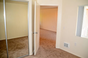 carpeted bedroom facing closet with mirrored door and door facing living room