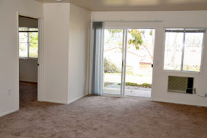 carpeted living room facing patio with sliding glass doors, window, build-in wall AC, and bedroom door