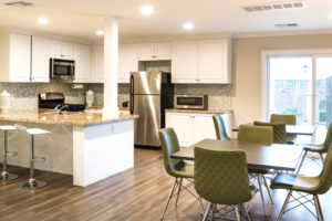 Large kitchen with granite countertops, white cabinets, gray hardwood floor, dining area with tables and green chairs