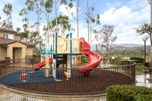 Children's playground with slide and various jungle gym equipment with view of mountains