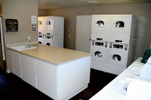 The Terraces laundry room with 11+ machines, an island in the middle of the room with a sink and paper towel dispenser