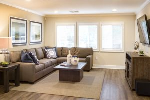 Lounge room with couch, coffee table, side table, decor, television, and bright windows