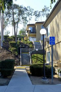 exterior of staircase up hill with trees and shrubs, sidewalk with outdoor lighting leading to parking area with handicap parking sign