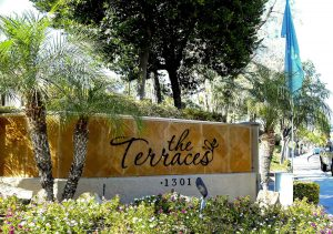 Tiled brown The Terraces sign with 1301 number surrounded by palm trees and plants