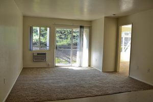 carpeted living room facing sliding glass door to patio, window and built-in wall AC